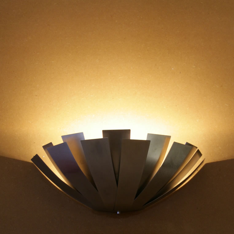 & Design wall light directing light upward providing ambient light